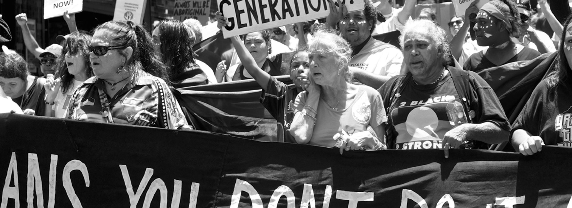"""Crowd protesting. A sign held up reads """"How many stolen generations?"""""""