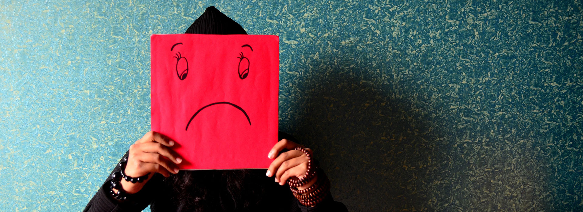 A person holding up a red square in front of their face with a sad face drawn on it.