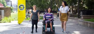 Three women walking alongside each other. One is vision impaired and is holding a stick, one is in an electronic wheelchair and the other is able bodied.