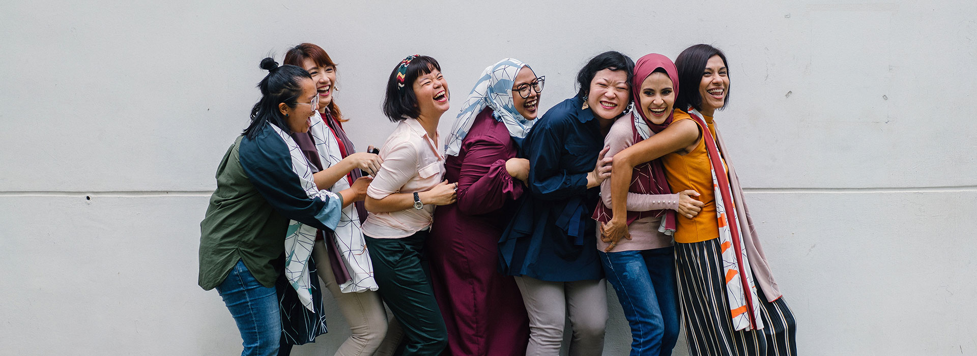 A group of culturally diverse women candidly hugging and laughing.