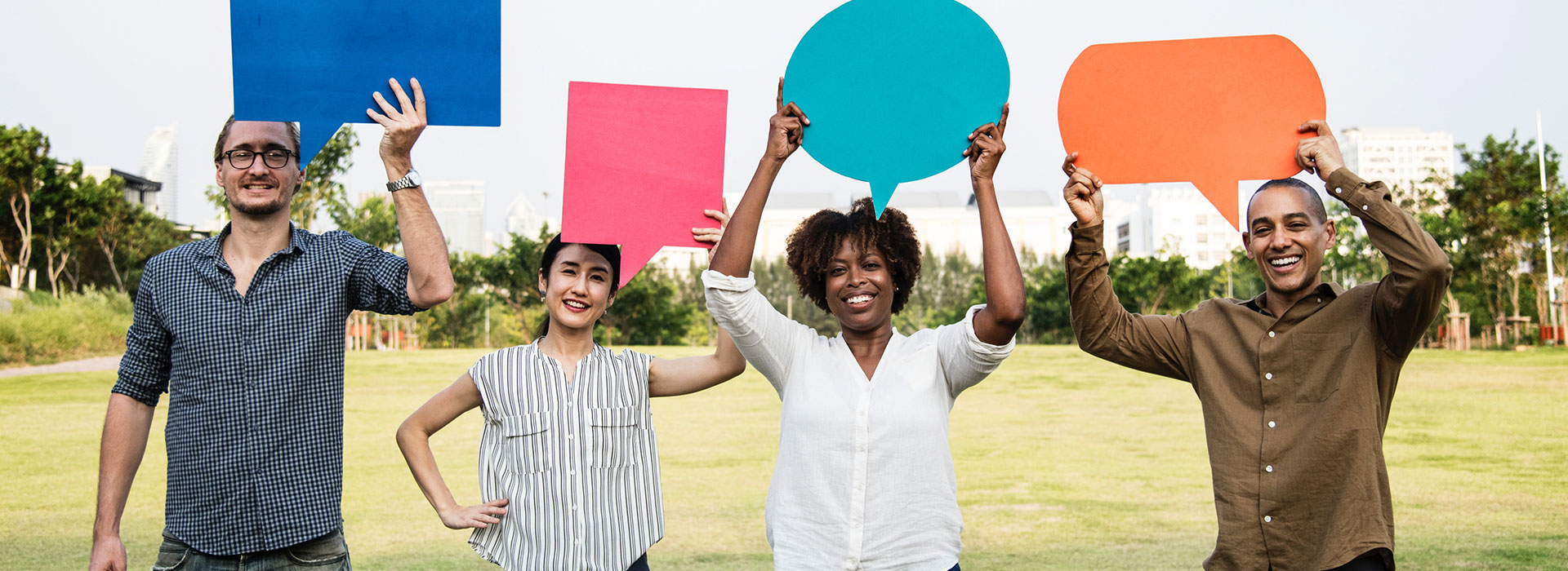 Four diverse individuals standing next to each other, smiling and holding coloured speech bubbles above their heads.