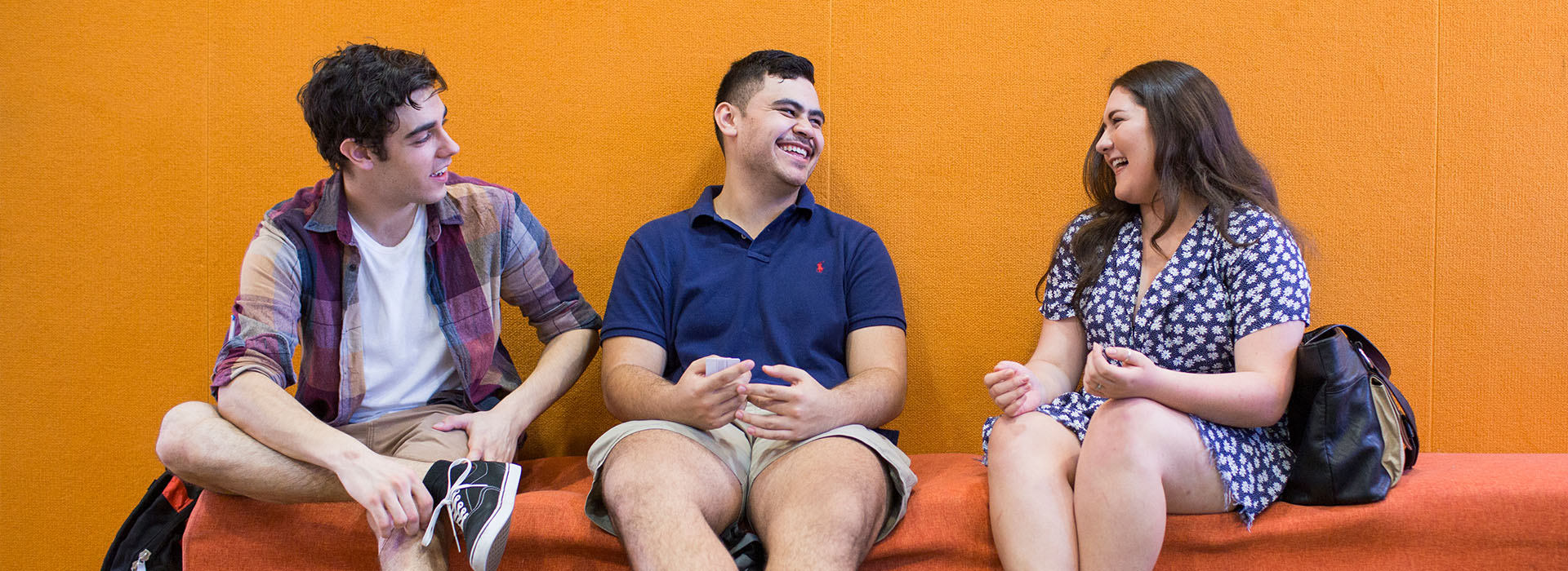 Three students talking and laughing. The wall behind them is bright orange.