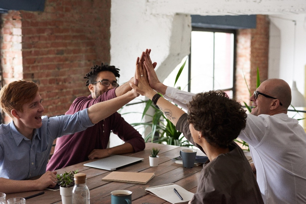 Group of people giving a high five over a desk