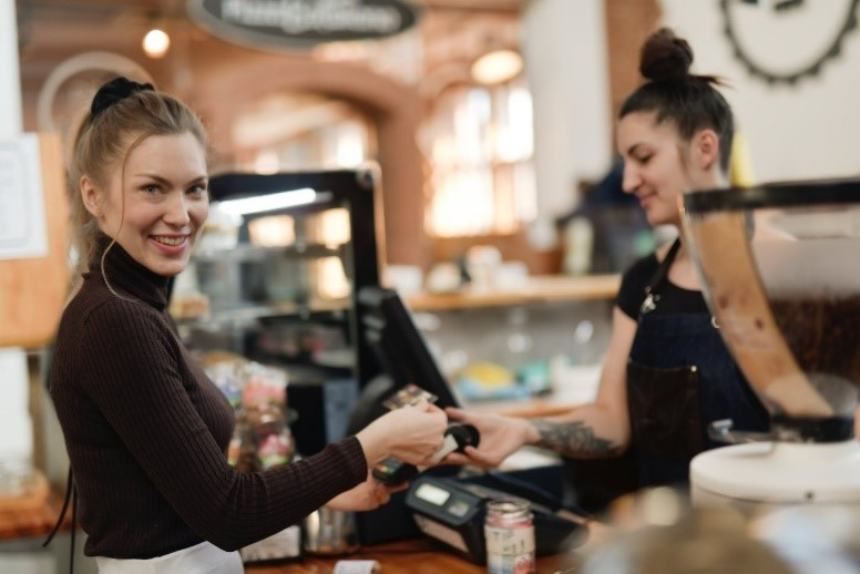 White lady working at coffee shop smiling over shoulder