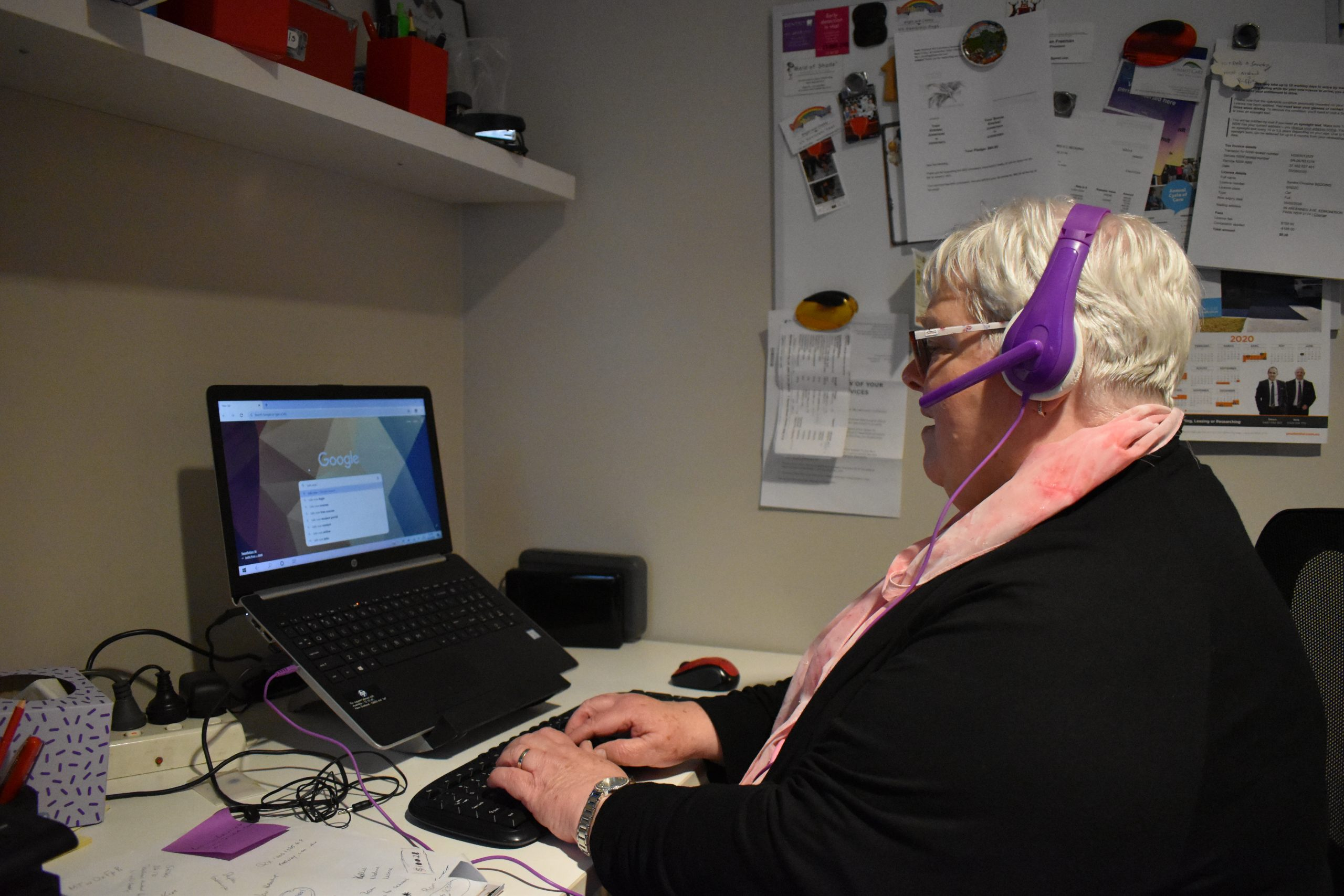 Woman at computer with purple headphones