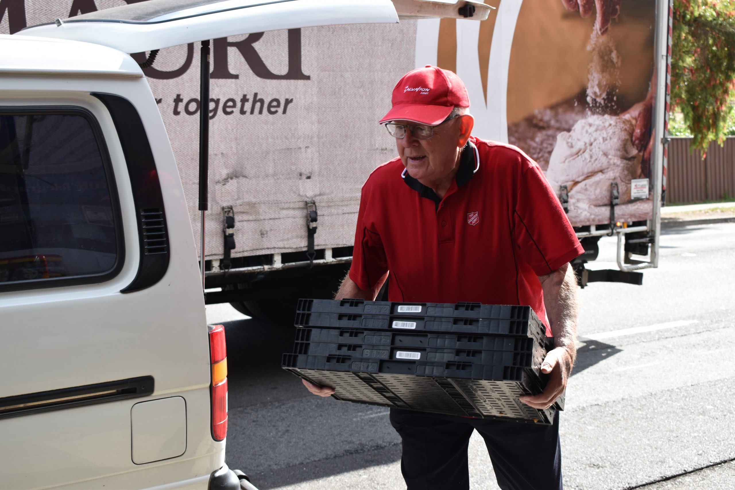 Hilton unloading crates from the back of his van