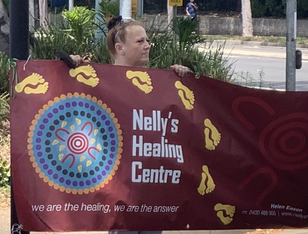 A woman, Kat Armstrong, holding a banner for Nelly's Healing Centre at the demonstration in Silverwater.