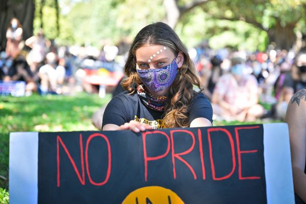 A young woman wearing a facemask stares down the camera holding a sign saying 'No Pride in Genocide'