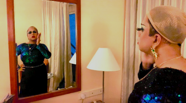 A drag queen looking into the mirror and applying makeup.
