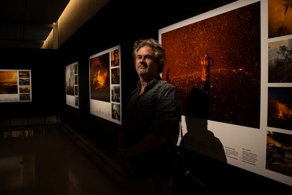 Moir stands in front of his photograph of the Green Wattle Creek fire, which he took mid-escape | Rafqa Touma