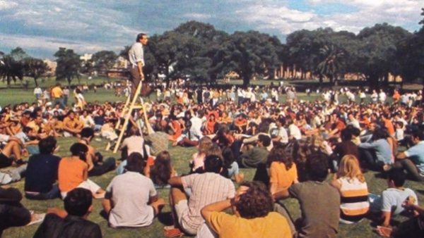 archival image of speaker addressing large crowd in the 1970s