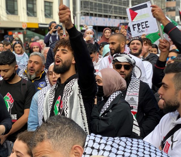 Protesters chanting, holding up Palestinian flag