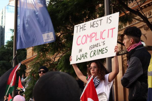 Girl carries sign reading 'The West is COMPLICIT in Israel's war crimes' in red and black.