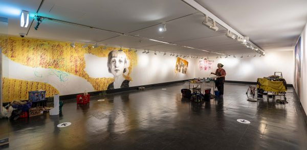 Wide shot of the gallery with mural