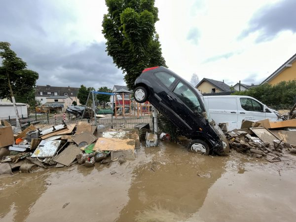 A car stands at a 45 degree angle, stuck in mud with debris everywhere