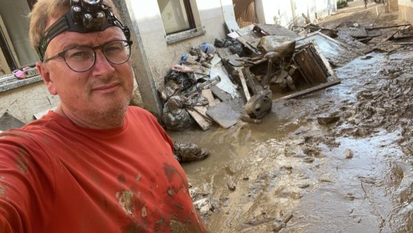 Ralf Breuer takes a snap of himself in thick mud while he's helping with the clean up after the floods.