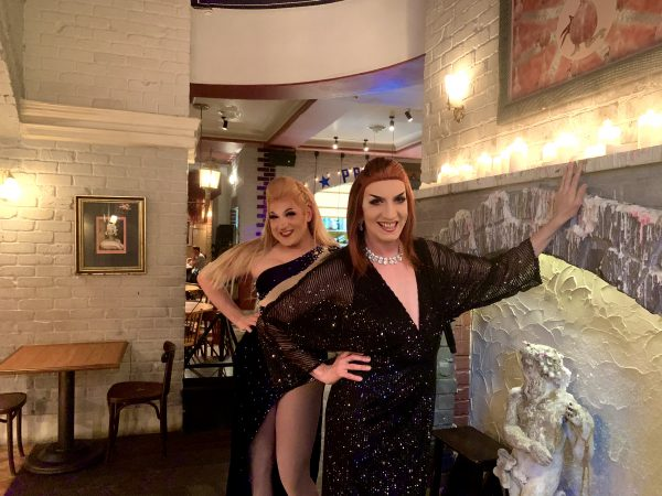 Two drag queens lean against the bar of The Imperial Hotel.