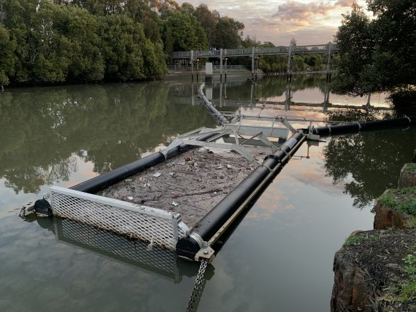 A Litter Trap and Boom, filled with rubbish and sediment