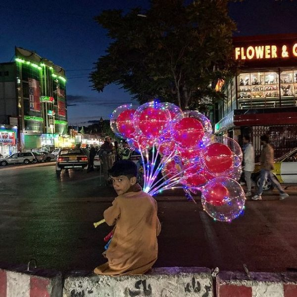 Boy with brightly coloured balloons in the street at night